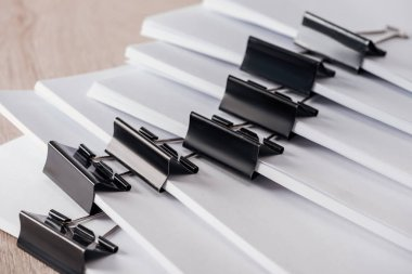 close up view of stacks of blank paper with metal binder clips