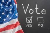 Nejlepší pohled na bílé písmo pro hlasování a zaškrtnutí vedle Yes slovo na černém křídu blízko americké vlajky