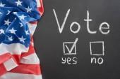 Nejlepší pohled na písmo hlasování a zaškrtávací značka poblíž Ano slovo na černém křídu blízko americké vlajky