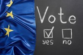 top view of vote lettering and check mark near yes word on black chalkboard near European flag