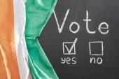 Nejlepší pohled na písmo pro hlasování a zaškrtnutí vedle Yes slovo na černém křídu u irské vlajky