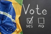 Photo top view of white vote word and check mark near yes word on black chalkboard near flag of Brazil
