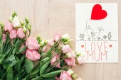 Fotografie top view of pink eustoma flowers and card with love mum words on wooden table