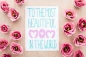 Fotografie pohled na růžovou eustomii a kartu s nejkrásnější matkou na světě nápisy na stole