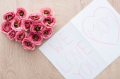 top view of heart-shaped eustoma flowers and card with we love you mom lettering on table