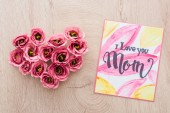 top view of heart sign made of eustoma flowers and card with i love you mom lettering on wooden surface