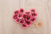 top view of heart sign made of eustoma flowers with happy mothers day paper label on wooden table