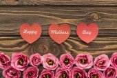 top view of pink eustoma flowers and red paper hearts with happy mothers day lettering on wooden table