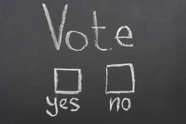 top view of white vote, yes and no lettering on black chalkboard