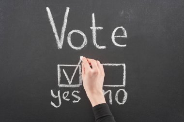 top view of voter putting check mark near yes word on black chalkboard