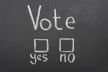 top view of white vote, yes and no words on black chalkboard