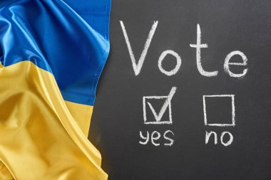 top view of vote lettering and check mark near yes word on black chalkboard near Ukrainian flag