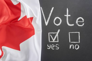 top view of vote lettering and check mark near yes word on black chalkboard near Canadian flag