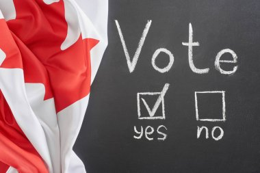 top view of white vote lettering and check mark near yes word on black chalkboard near Canadian flag