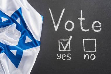 top view of white vote lettering and check mark near yes word on black chalkboard near flag of Israel