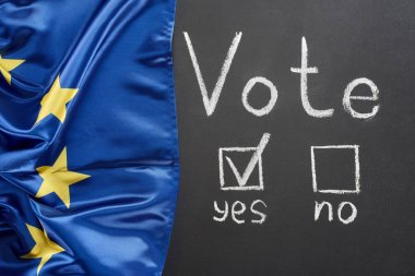top view of vote lettering and check mark near yes word on black chalkboard near flag of Europe