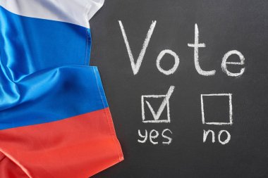 top view of vote lettering and check mark near yes word on black chalkboard near flag of Russia