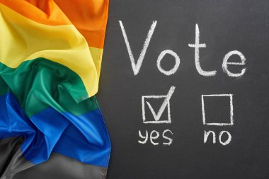 top view of vote lettering and check mark near yes word on black chalkboard near lgbt flag