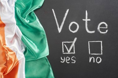 top view of white vote lettering and check mark near yes word on black chalkboard near flag of Ireland