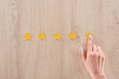 cropped view of woman pointing with finger at yellow star on wooden table
