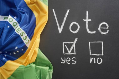 top view of white vote lettering and check mark near yes word on black chalkboard near flag of Brazil