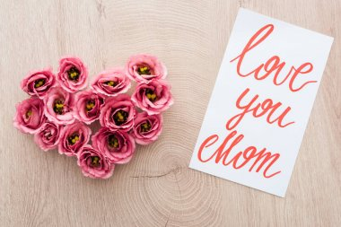 Top view of heart sign made of eustoma flowers and card with love you mom lettering on wooden table stock vector
