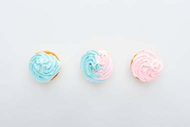 top view of delicious colorful cupcakes with sprinkles in row Isolated On White