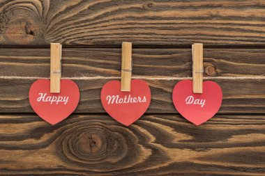 Top view of clothes pegs and red paper cards with happy mothers day writing on wooden table stock vector