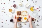vágott kilátás a nő tetoválással a kézben gazdaságban tányér ízletes reggelivel, fehér