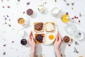 vágott kilátás a nő tetoválással a kezében tartó tányér reggelivel fehér
