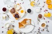 Nejlepší pohled na talíře s chutnými toasty v blízkosti nápojů a pomerančů na bílém