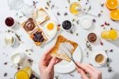 oříznutý pohled ženy rozmetání sýra na chutný toast na bílém