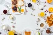 pohled na talíře s chutnými toasty v blízkosti nápojů a misky s marmeládou na bílém