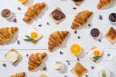 Nejlepší pohled na sladké croissanty a chutné toasty s arugulskou Listinou v blízkosti sušených květin na bílém
