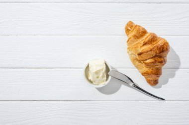 top view of knife near bowl with cream cheese and croissant on white