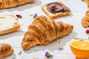 selective focus of croissant near toast with chocolate cream on white