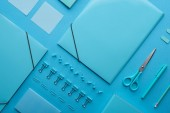 flat lay of paper binders and various arranged stationery isolated on blue