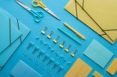 top view of colorful paper clips, scissors, paper folders and various stationery isolated on blue