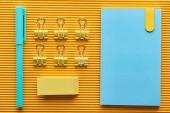 Nejlepší pohled na pero, notebook a barevnou kancelářskou šablonu na žlutou