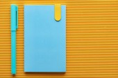 top view of blue pen and notebook on yellow with copy space