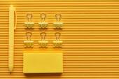 Fényképek felülnézet toll, gemkapcsok és színes rendezett irodai írószerek a sárga