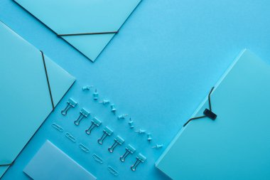 flat lay of paper folders and various stationery isolated on blue