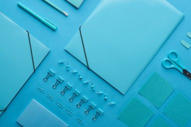 flat lay of paper binders and organized stationery isolated on blue
