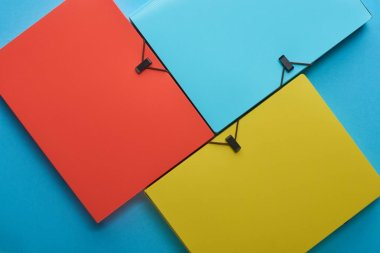 top view of arranged colorful paper folders on blue