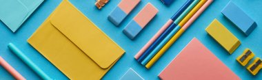 panoramic shot of envelope and arranged colorful stationery isolated on blue