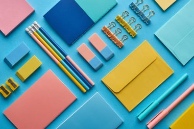 top view of notebooks and arranged colorful stationery isolated on blue