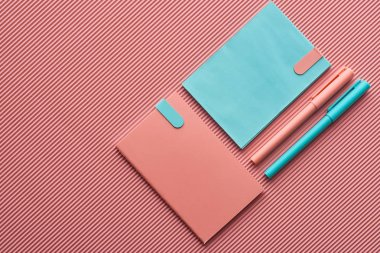top view of pens and notebooks on textured pink