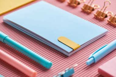 selective focus of notebook and colorful stationery supplies on pink