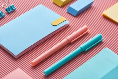 colorful pens, notebooks and erasers on pink