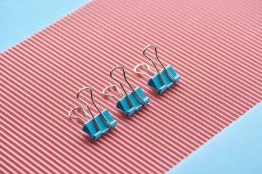 metal paper clips on textured pink paper isolated on blue